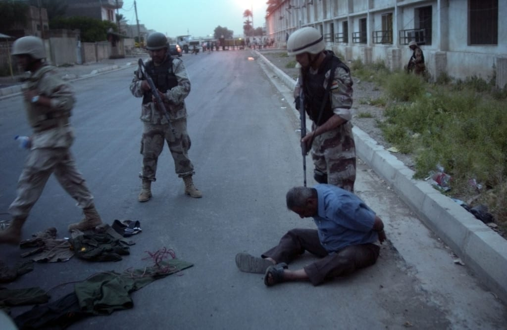 Photojournalists embedded with the US military say they have felt free to take and publish potentially damaging images. Here a civilian driver with a trunk of (old) Iraqi Army uniforms is arrested and beaten by a translator. Joint US/Iraqi National Government patrol, Baghdad, 24 April 2005. Image © Thomas Dworzak/Magnum Photos.