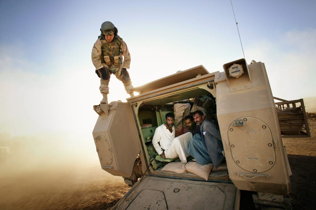 Tal Afar, June 2005: Suspected insurgents are detained inside a Bradley Fighting Vehicle to be transported to a detention facility during an early morning raid. Soldiers from the 3d Armored Cavalry Regiment and Iraqi soldiers moved into Tal Afar with Bradleys, tanks and Humvees. Helicopters provided air support as the soldiers searched houses and detained suspects. Image © Christoph Bangert