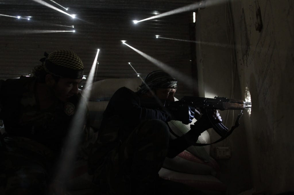 Two rebel soldiers in Syria guard their sniper's nest in the Karmel Jabl neighbourhood of Aleppo as light streams through more than a dozen holes made by bullets and shrapnel in the tin wall behind them. The dust from more than one hundred days of shelling, bombing and firefights hangs in the air. Karmel Jabl is strategically important because of its proximity to the main road that separates several of the main battlegrounds in the city. Both sides (the Free Syria Army and the regime) rely heavily on snipers in a cat-and-mouse game along Aleppo's frontlines. Image © Javier Manzano / AFP.