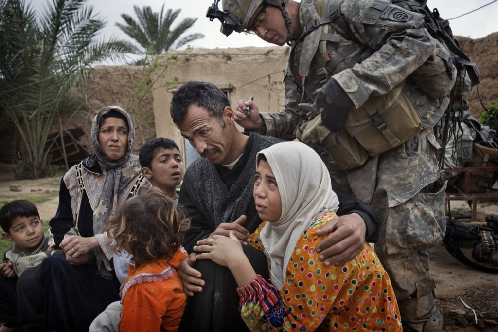 Qubah, 24 March, 2007: A US soldier marks numbers on to the hands of women and the backs of the necks of men, indicating their specific neighbourhoods and homes. Lt Col Andrew Poppas of the 73rd Cavalry, 82nd Airborne Division, said the numbering system allowed troops to determine if people were moving around the village of Qubah, despite a lockdown following a US attack on insurgents. Image © Yuri Kozyrev / Noor