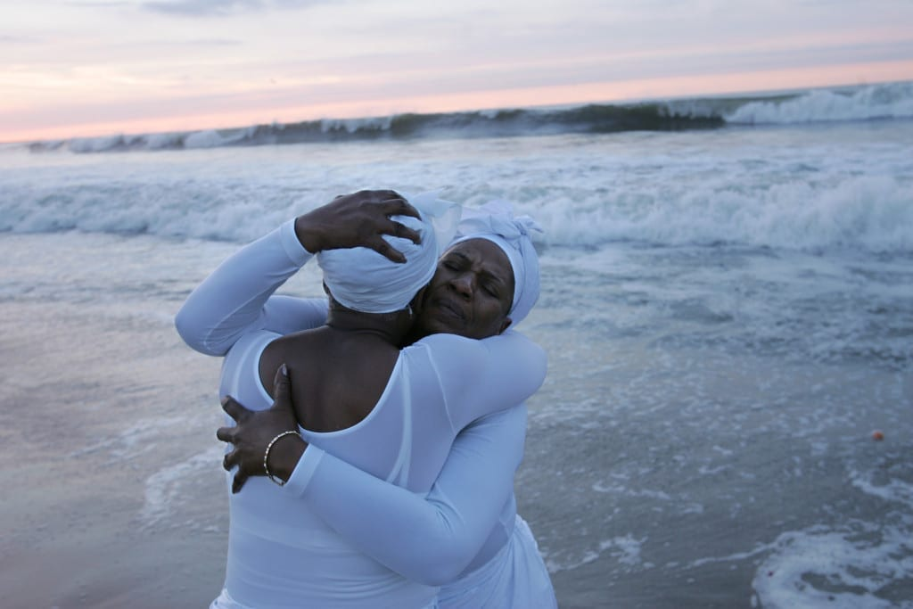 Members of St. Paul's Church embrace at a seaside Maafa ceremony in Queens, in observance of the those who died during the Middle Passage and in slavery in the United States. 2004 © James Estrin / The New York Times