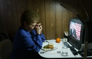 Marge Marcone saying grace over her hot dinner, which was delivered to her Bronx apartment by Meals on Wheels, a charitable organization. 2004 © James Estrin / The New York Times