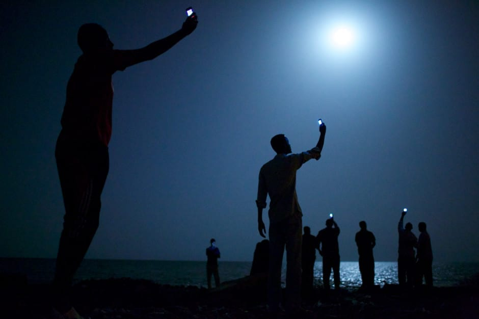 World Press Photo of the Year 2013: 26 February 2013, Djibouti City, Djibouti African migrants on the shore of Djibouti city at night, raising their phones in an attempt to capture an inexpensive signal from neighboring Somalia—a tenuous link to relatives abroad. Djibouti is a common stop-off point for migrants in transit from such countries as Somalia, Ethiopia and Eritrea, seeking a better life in Europe and the Middle East © John Stanmeyer, USA, VII for National Geographic