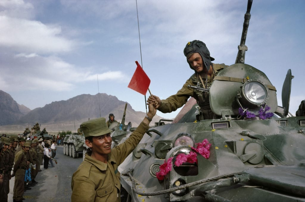May 1988: An Afghan soldier hands a flag in solidarity to a departing Soviet soldier in Kabul on the first day of the army's withdrawal from Afghanistan © Robert Nickelsberg