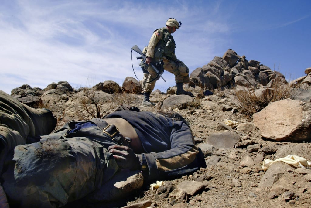 March 2002: US Army Sergeant Major Dennis Carey of the 10th Mountain Division looks over a dead al Qaeda or Taliban fighter March 16, 2002 in the Shah-i-Kot Valley, Afghanistan. The position was involved in heavy firing against US soldiers when Operation Anaconda began March 2, 2002. US Air Force planes took out the position. It is believed Arab and Chechen members of al Qaeda occupied Shah-i-Kot Valley positions © Robert Nickelsberg