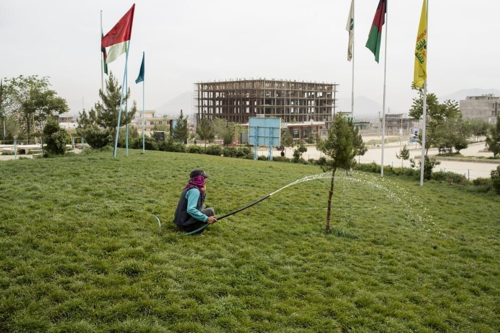 May 2013: A gardener speaks on his cell phone while watering a park in the newly-developed Omid-e Sabz district of western Kabul © Robert Nickelsberg