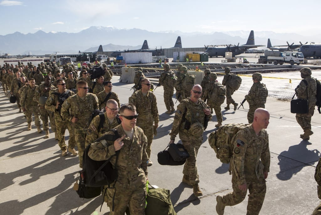 May 2013: A contingent of American troops conclude their tour in Afghanistan and prepare to fly home from Bagram Air Base. Others arrive, wearing their helmets © Robert Nickelsberg