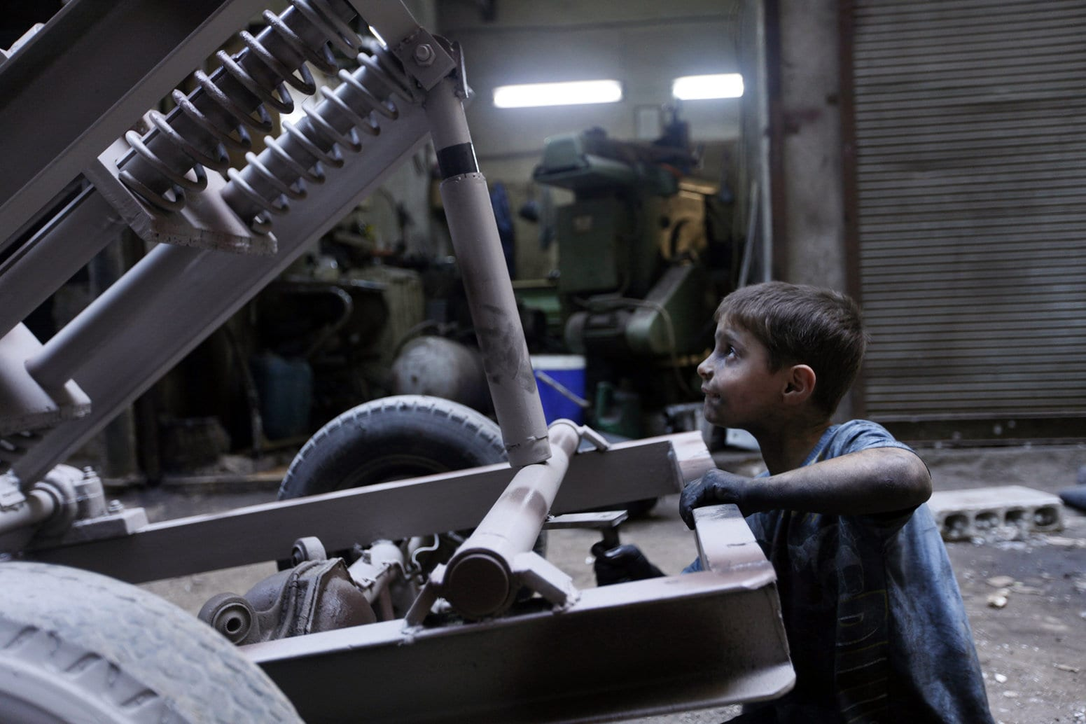 Issa, 10 years old, fixes a mortar launcher in a weapons factory of the Free Syrian Army in Aleppo, September 7, 2013. Issa works with his father in the factory for ten hours every day except on Fridays. (REUTERS/Hamid Khatib)