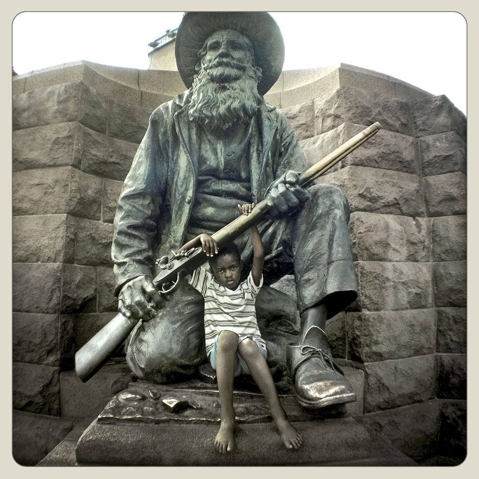 Elia Mashao on statue of Boer soldier  - Church Square, Tshwane © Dale Yudelman, from the series Life under Democracy