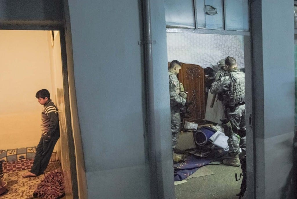 American soldiers on a foot patrol noticed that two young men were eying them and fidgeting. Anticipating violence, they stormed their house. During the search the soldiers teased a young medic about his virginity. The soldiers had already searched hundreds of houses during their deployment, and the banter was casual as they swept the family's possessions onto the floor. MOSUL. IRAQ. 2006 © Peter van Agtmael from the book Disco Night Sept 11 (Red Hook Editions).