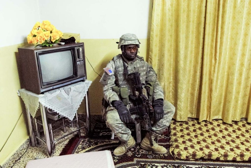 Sergeant Jackson rests while his platoon searches the house of a suspected insurgent. They found nothing suspicious, and the commander assumed he had received bad intelligence. Most of the raids I witnessed were dry holes. Before leaving, the commanding officer would occasionally compensate for damage by pressing a wad of soiled dinars or dollars into wary hands. Usually the platoon would leave without an apology to continue searching for their target, or return to base before insurgents had the chance to organize and attack. RAWAH. IRAQ. 2006 © Peter van Agtmael from the book Disco Night Sept 11 (Red Hook Editions).