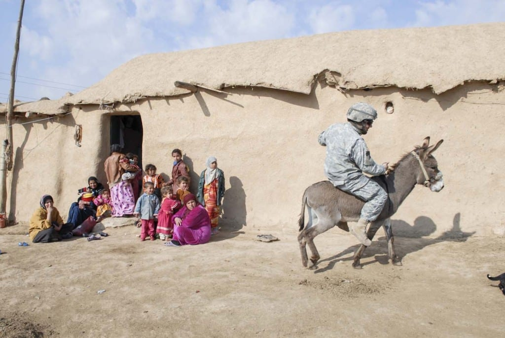 A soldier rides a donkey in Nineveh. The wary inhabitants of the isolated village had never seen an American patrol, and asked what country they were from. They served sugary tea to the soldiers but otherwise kept their distance. The troops took turns riding the donkey and posed for pictures holding lambs. In the Bible, Nineveh is described as a wicked city. God sent the prophet Jonah to preach there, and its inhabitants repented. God decided to spare the city. NINEVEH. IRAQ. 2006 © Peter van Agtmael from the book Disco Night Sept 11 (Red Hook Editions).