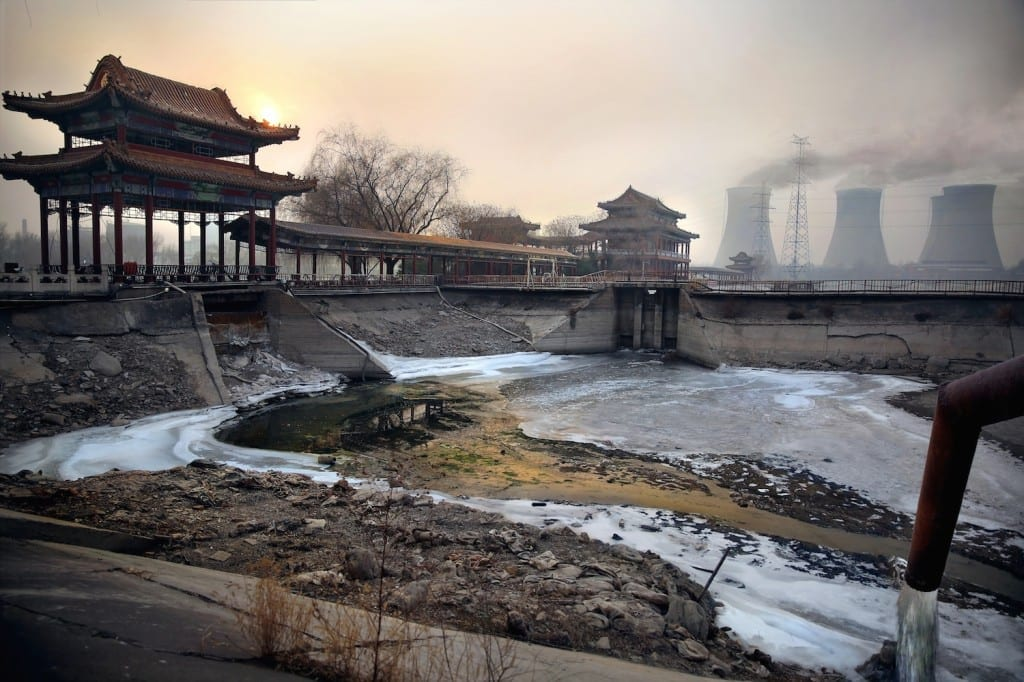 The Shuogang group steel factory on the outskirts of Beijing. Despite the government promising to close all major polluting factories within city limits following the 2008 Olympics, several are still operating behind closed doors. At dawn every day, the factory waste-water pipe illegally spews hazardous chemicals into a local dried up lake. The accumulated green and brown deposits contain poisonous heavy metal deposits that are visible here. Image © Souvid Datta