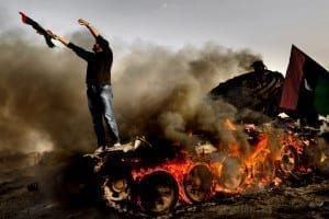 In February 2011, the Arab Spring spread to Libya. After a week-long siege, the town of Ajdabiya fell when French aircraft bombed the Gaddafi-loyalist troops. Here, a local man is pictured thanking God for the victory while standing on a burning tank. He was aware of Mads Nissen, the photographer, so he was actively presenting an image of himself for the camera. Image © Mads Nissen, courtesy Panos Pictures