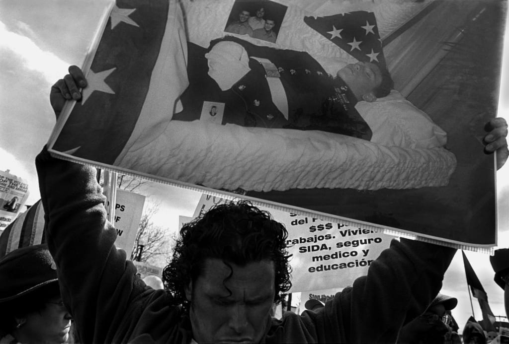 Jamaica Plain, Massachusetts, March 2006. Carlos Arredondo carries a a photograph of his son Alex in a coffin, in a rally marking the eve of the third anniversary of the U.S.-led bombing and invasion of Iraq. Twenty-year-old Lance Corporal Alexander Arredondo, a Marine, was killed in combat in An Najaf, Iraq on August 25, 2004, his father's 44th birthday. Image by Eugene Richards/Getty Images Grant recipient 2013