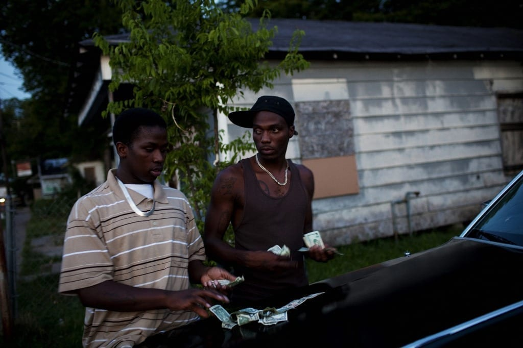 """'Sin and Salvation in Baptist Town': Demetrius """"Butta"""" Anderson, 18, and Roger """"Winky"""" Williams count money on a friend's car before a night of smoking, drinking and gambling in front of Hoover's Store in the Baptist Town neighborhood of Greenwood, Mississippi on July 2, 2010. Butta was shot and killed in October, becoming the third person in his family to be murdered. Image by Matt Eich/Getty Images Grant recipient 2013"""