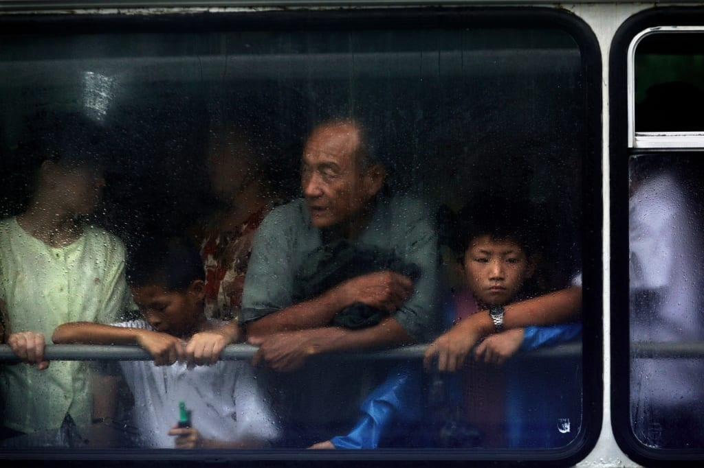 Passengers look out from a bus window in the rain in Pyongyang, North Korea (DPRK) on 14 August 2007. © Tomas van Houtryve/ Getty Images Grant recipient 2013