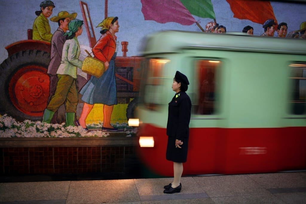 An attendant stands near the tracks as a metro train arrives in the station in the subway of Pyongyang, North Korea (DPRK) on 20 August 2007. © Tomas van Houtryve/ Getty Images Grant recipient 2013