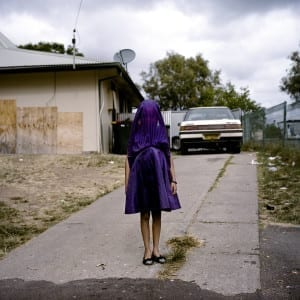 First Prize Portraits Category, Singles: Raphaela Rosella, Australia. Laurinda waits in her purple dress for the bus that will take her to Sunday School in Moree, New South Wales. She is among the many socially isolated young women in disadvantaged communities in Australia facing entrenched poverty, racism, trans-generational trauma, violence, addiction, and a range of other barriers to health and well-being. © Raphaela Rosella