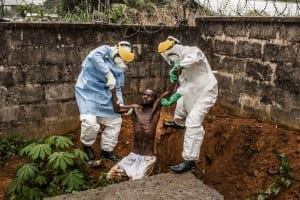 Ebola Virus for National Geographic Magazine. Medical staff at the Hastings Ebola Treatment Center escort a man in the throes of Ebola-induced delirium back into the isolation ward from which he escaped in Hastings, Sierra Leone, on Sunday, 23 November 2014. In a state of confusion, he emerged from the isolation ward and attempted to escape over the back wall of the complex before collapsing in a convulsive state. A complete breakdown of mental facilities is a common stage of advanced Ebola. The man pictured here died shortly after this picture was taken. © Pete Muller / Prime for National Geographic