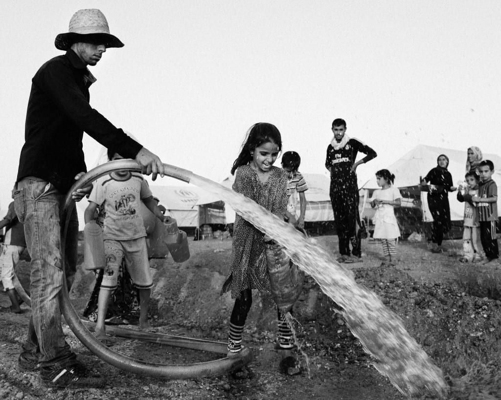 A Yazidi girl, smiling as she tries to get water for her family in Dohuk