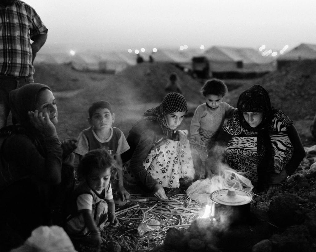 A Yazidi family cook dinner in a UN camp in Zakho