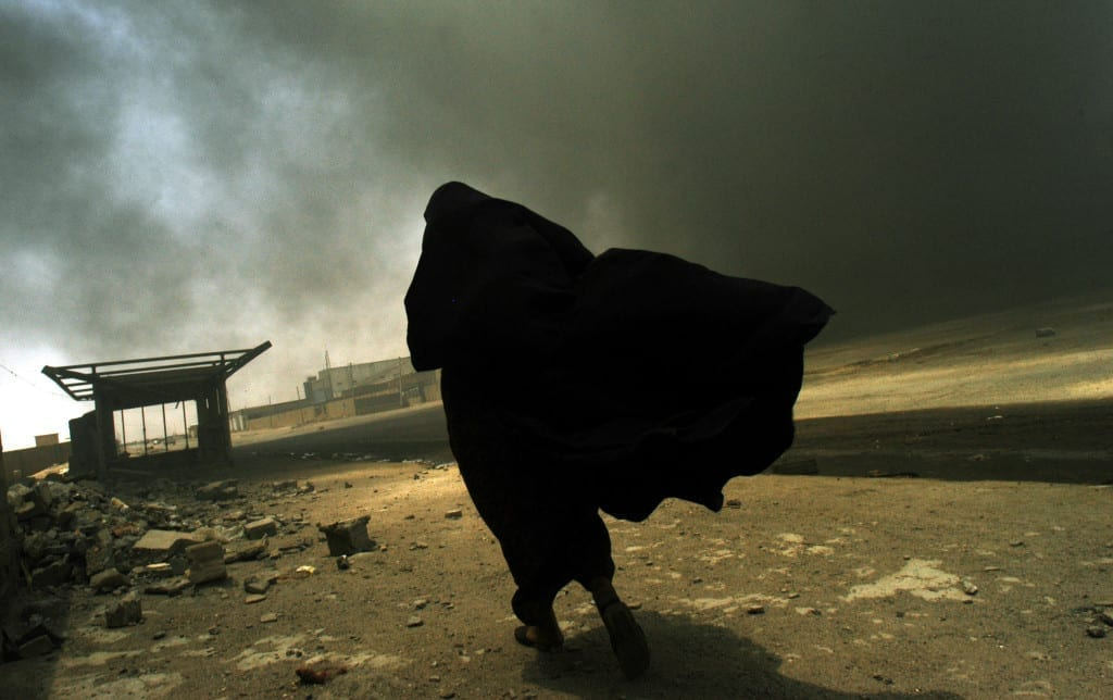 An Iraqi woman searching for her husband walks through the smoke rising from a fire at a gas factory on May 26, 2003 in Basra, Iraq.