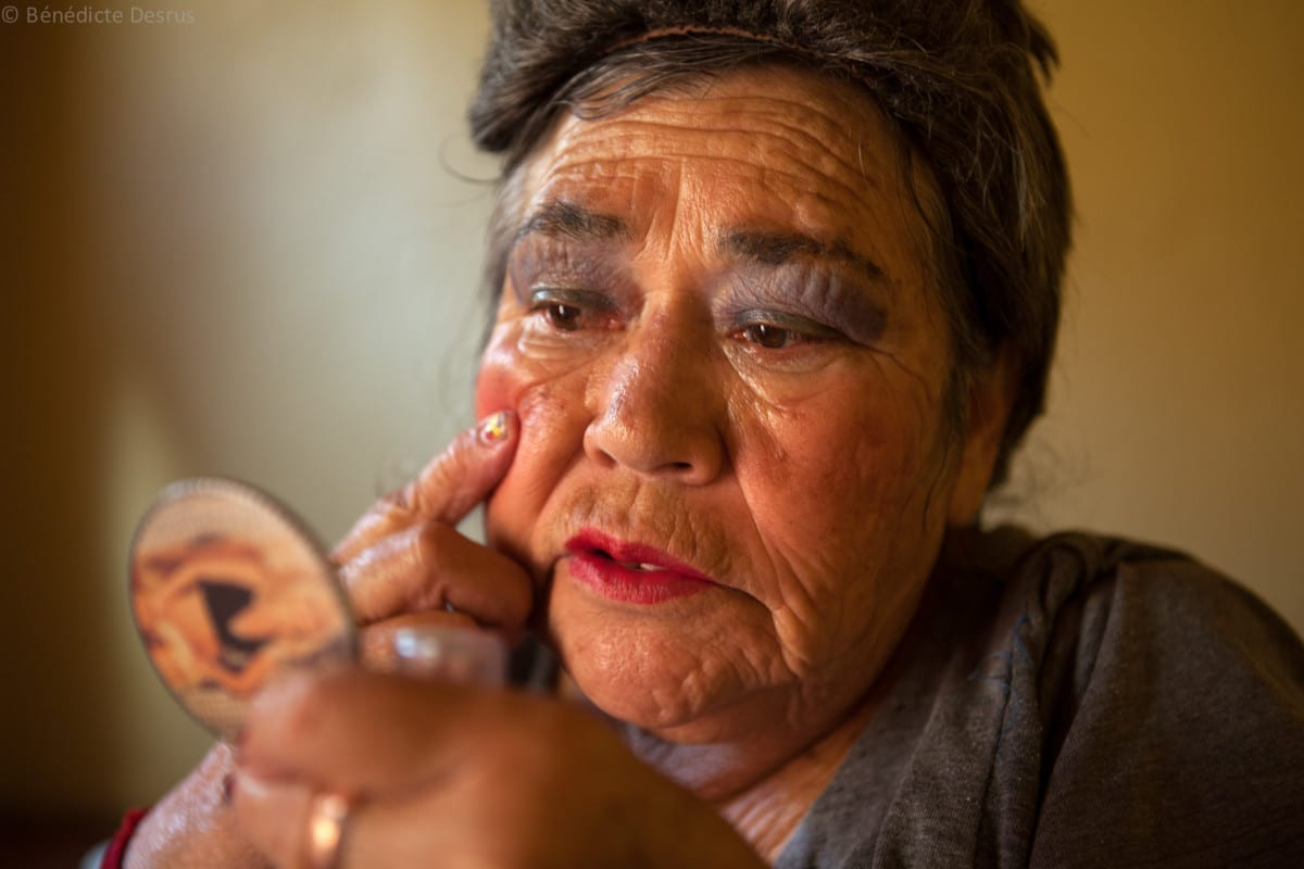 Amalia, a resident of Casa Xochiquetzal, puts on makeup before going out to work on the streets of the La Merced neighborhood of Mexico City on October 15, 2010. Amalia, 66, is from Michoacán and came to Casa Xochiquetzal when it first opened its doors. She wears a wig and pads her bra. She is very animated; words and songs come easily to her. She has also suffered from schizophrenia for 22 years, but despite hearing voices, she works hard not to lose touch with reality. As a way of earning a little money, she gathers plastic bottles to recycle and also helps to sell clothes in a stand operated by her boyfriend of 31 years.