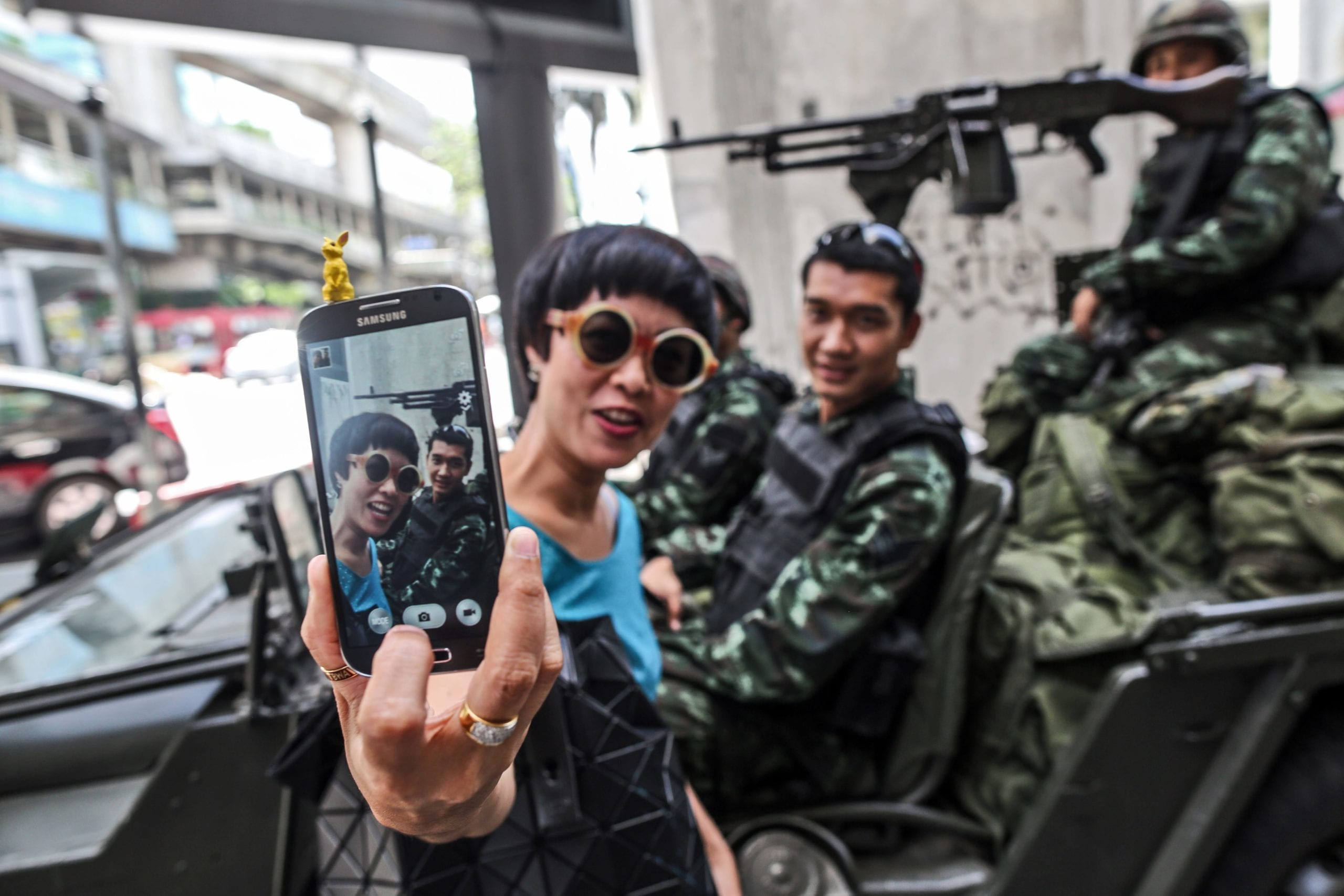 A women takes a selfie picture with Royal Thai Army soldiers stationed at the Ratchaprasong intersection, as martial law is imposed, in Bangkok, Thailand, on Tuesday, May 20, 2014.