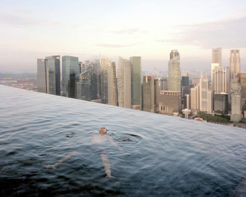 """A man floats in the 57th-floor swimming pool of the Marina Bay Sands Hotel, with the skyline of """"Central,"""" the Singapore financial district, behind him."""