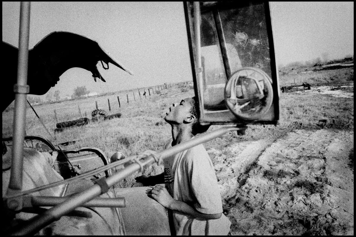 USA. Teviston, California. 2001. Boy with an old farm truck.