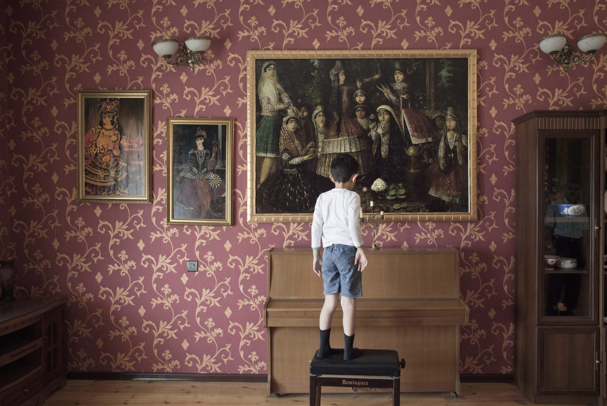 Youngest member of Kadjar family, who claim to be the royal family in Azerbaijan, stares at copies of ancient Iranian paintings in the family house in Baku. Azerbaijan. 2012