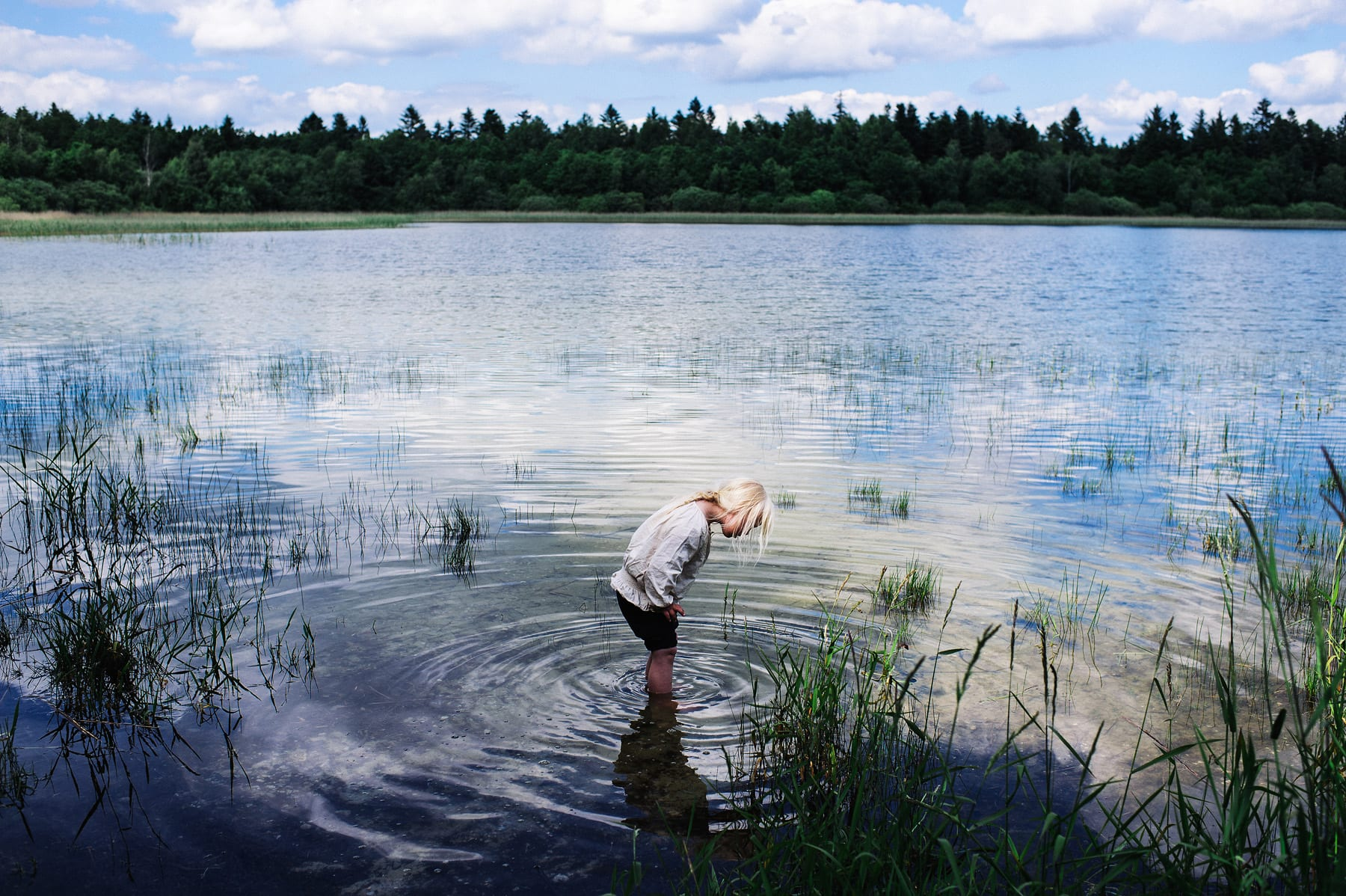 Europe, Denmark, Hampen Sø: Emmy is on a trip with her brother Kristian and her Grandmother. After playin in the forest for a while she cools down her feet in the lake. She looks through the clear water on the ground of the lake and explores the water very slowly.