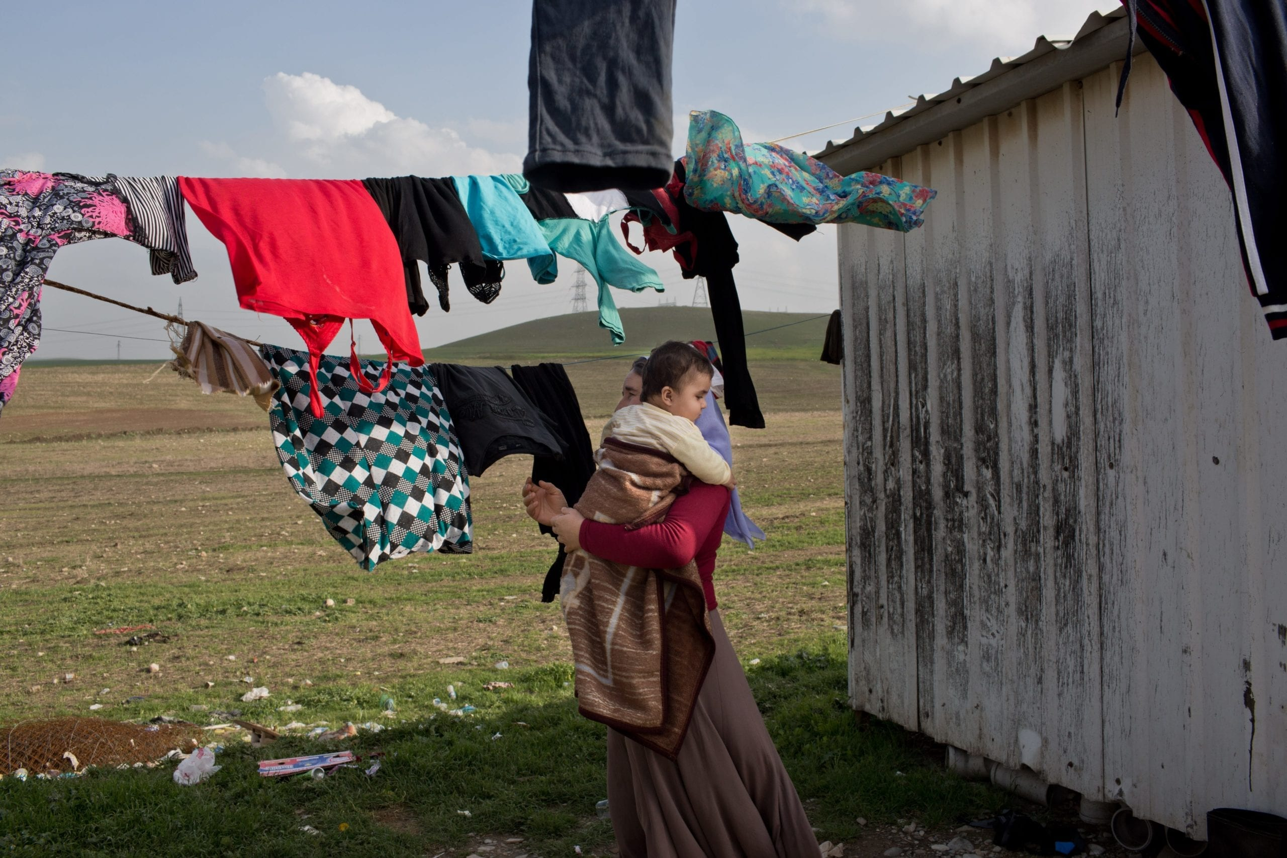 Ghazal hangs up the family laundry while holding her grandson, Mazal. The family of Yezidis, displaced from Sinjar, live next to an oil refinery in the Kurdish Region of Iraq. The young men run the refinery 24 hours a day with little to no safety equipment.