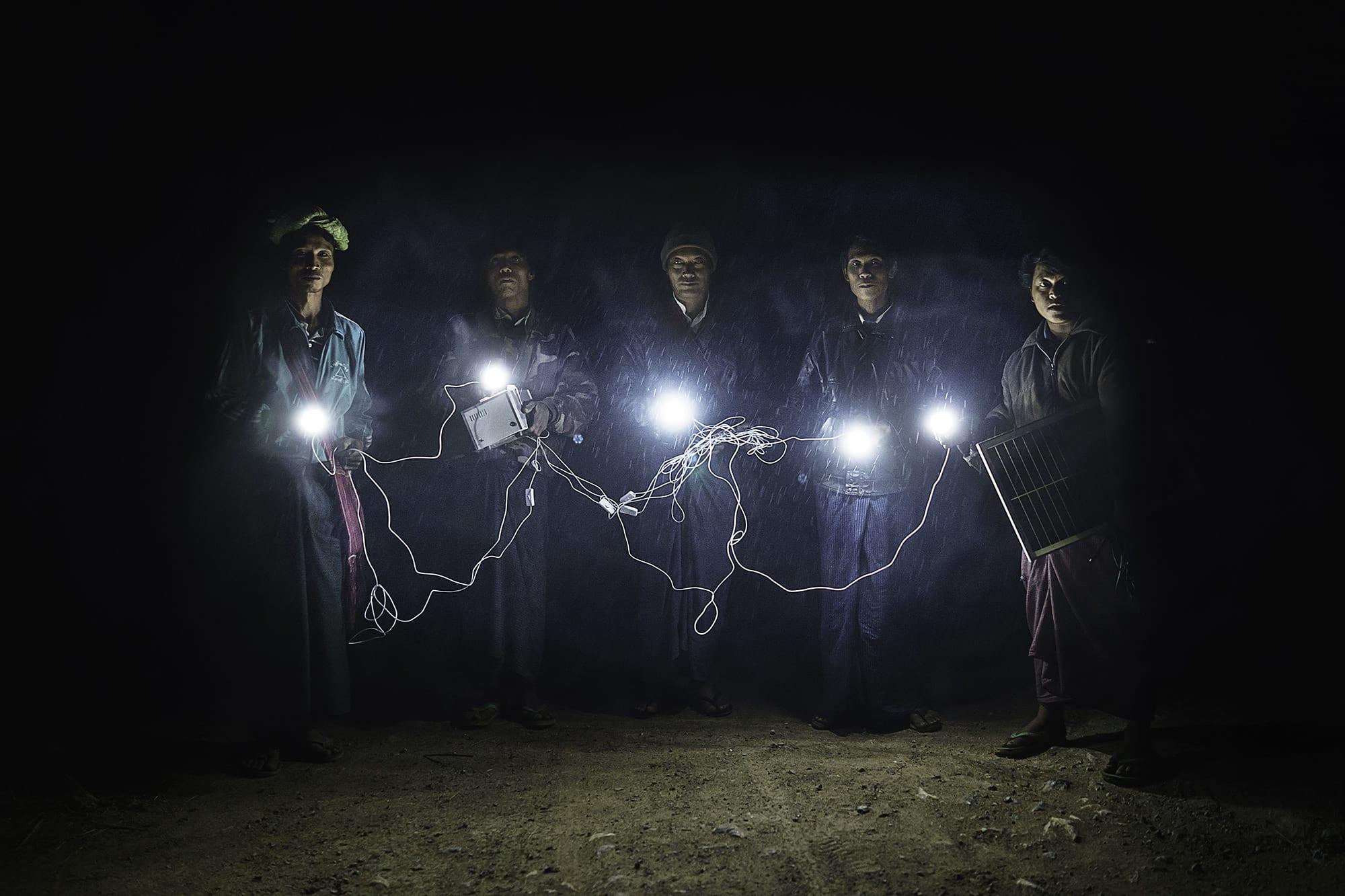Village leaders walk through Inn Gaung Village illuminated by a solar panel energy system.