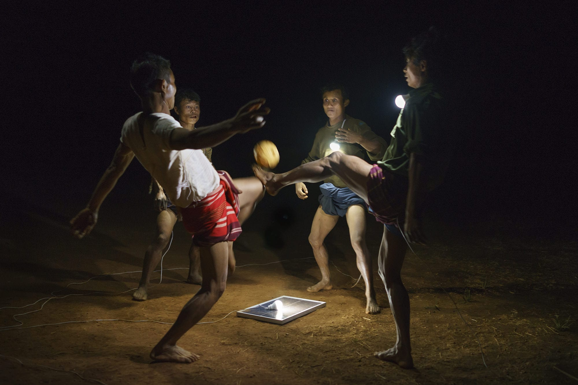 Men playing Chinlone, Myanmar's national sport on a field in Pa Dan Kho Village.