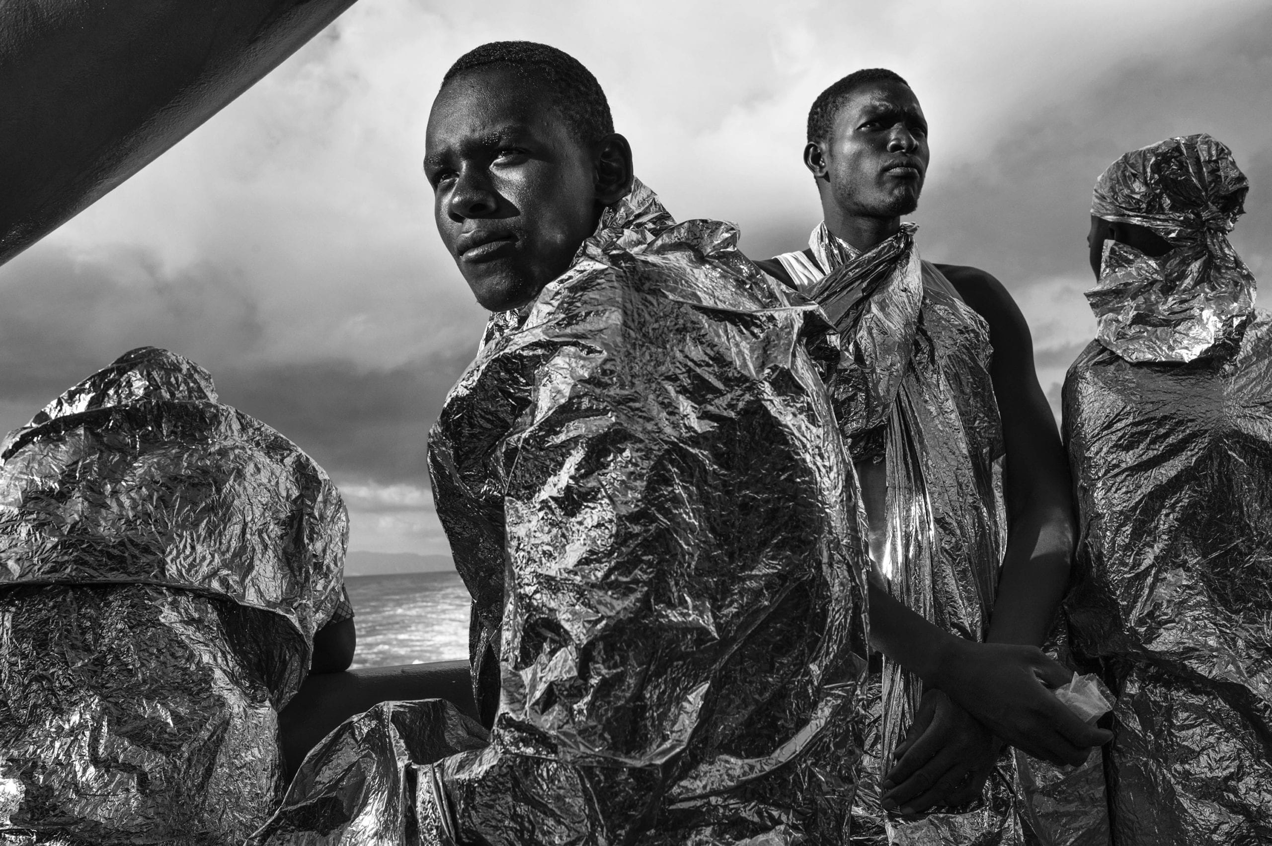 After spending two days and two nights sailing on the Mediterranean Sea on the deck of the M.S.F. (Médecins Sans Frontières - Doctors Without Borders) search and rescue ship Bourbon Argos, rescued migrants - still wrapped in their emergency blankets - catch sight of the Italian coast for the first time soon after dawn. 23 August 2015. In 2015 the ever-increasing number of migrants attempting to cross the Mediterranean Sea on unseaworthy vessels towards Europe led to an unprecedented crisis. Nearly 120 thousand people have reached Italy in the first 8 months of the year. While the European governments struggled to deal with the influx, the death toll in the Mediterranean reached record numbers. Early in May the international medical relief organization Médecins Sans Frontières (M.S.F.) joined in the search and rescue operations led in the Mediterranean Sea and launched three ships at different stages: the Phoenix (run by the Migrant Offshore Aid Station), the Bourbon Argos and Dignity (c) Francesco Zizola