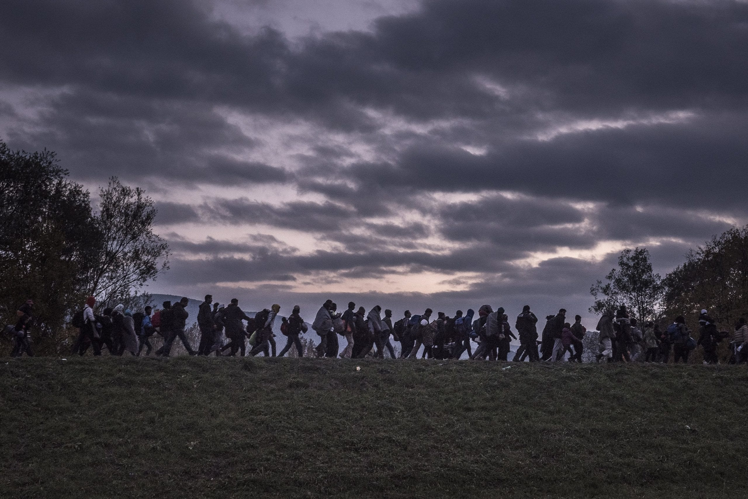 Migrants walked atop a dike as Slovenian riot police escorted them to a registration camp outside Dobova. War, drought and more are driving millions of people from their homelands © Sergey Ponomarev fo
