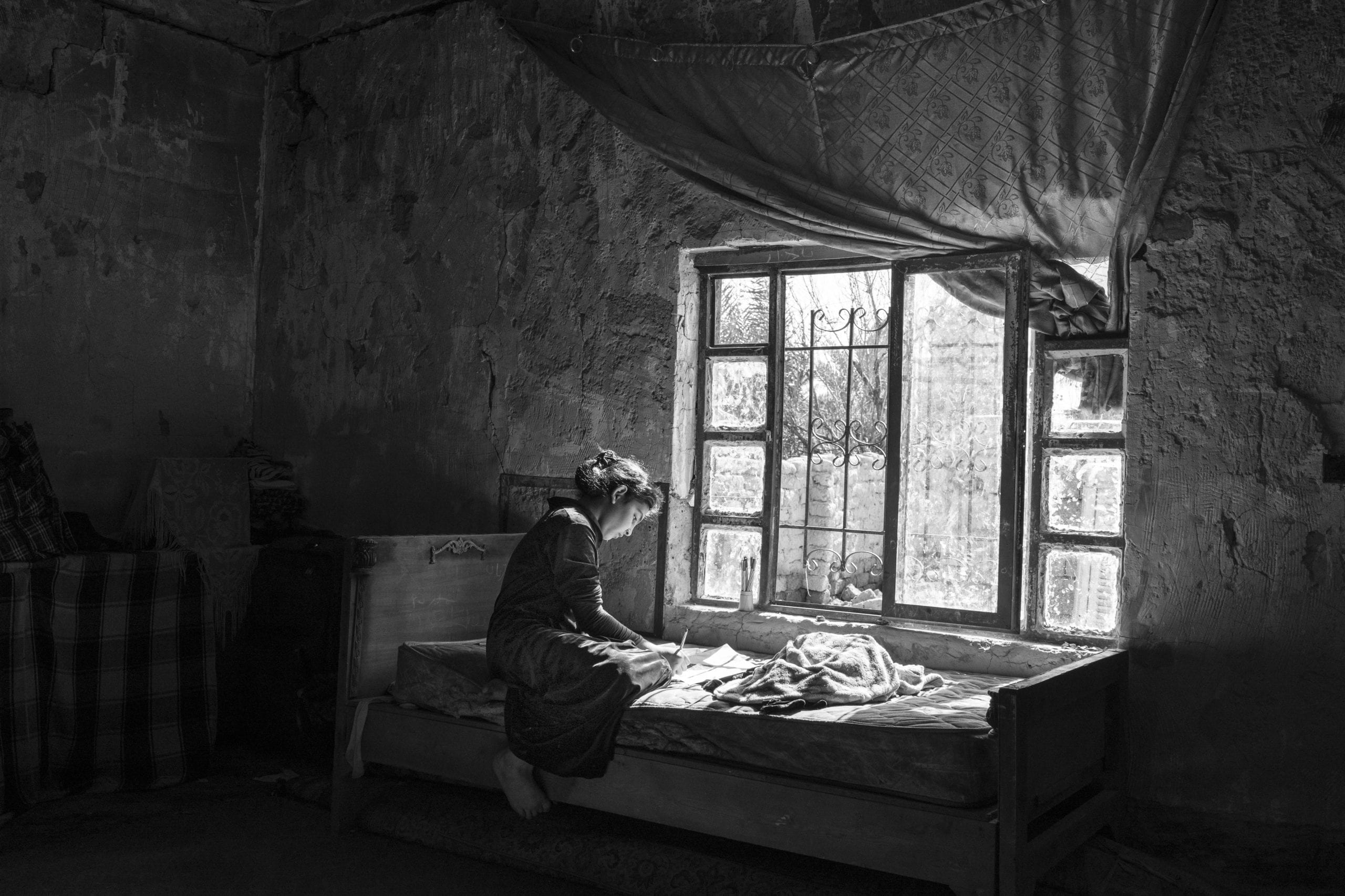 IRAQ. Albu Ajeel. February 2, 2016. 10-year-old Sara Adnan Mohamed, draws in a room in the partially burned down house that she shares with her family in the predominantly Sunni village of Albu Ajeel, on the outskirts of Tikrit. Albu Ajeel was under the control of the Islamic State until their retreat from Tikrit in the Spring of 2015..  Sara and her family recently returned to Albu Ajeel after being displaced to Kirkuk for almost two years. Upon their return, Sara's family found their village mostly destroyed and their home partially burned down.  In order to help Sara and other families cope, the International Committee of the Red Cross distributes food parcels to returnees and has also rehabilitated the water supply to Albu Ajeel residents.