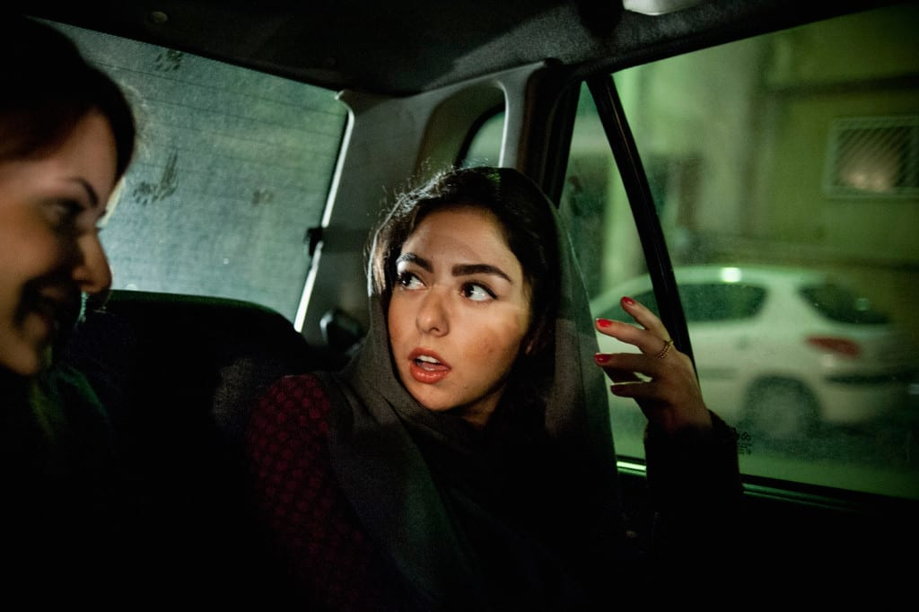 TEHRAN, IRAN | 2011-11-24 | Yassi and her friend take a cab to an opening reception at a gallery in northern Tehran. Even though being bold and eye-catching is always a factor that concerns the morality police, many girls choose to put on bright lipstick and wear distinctive fashion.