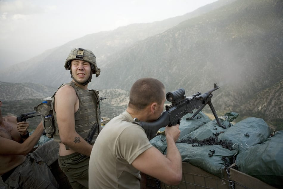 Misha Pemble is startled by the sound of gunfire during a firefight across the valley with insurgents. Korengal Valley, Kunar Province, Afghanistan. June 2008.
