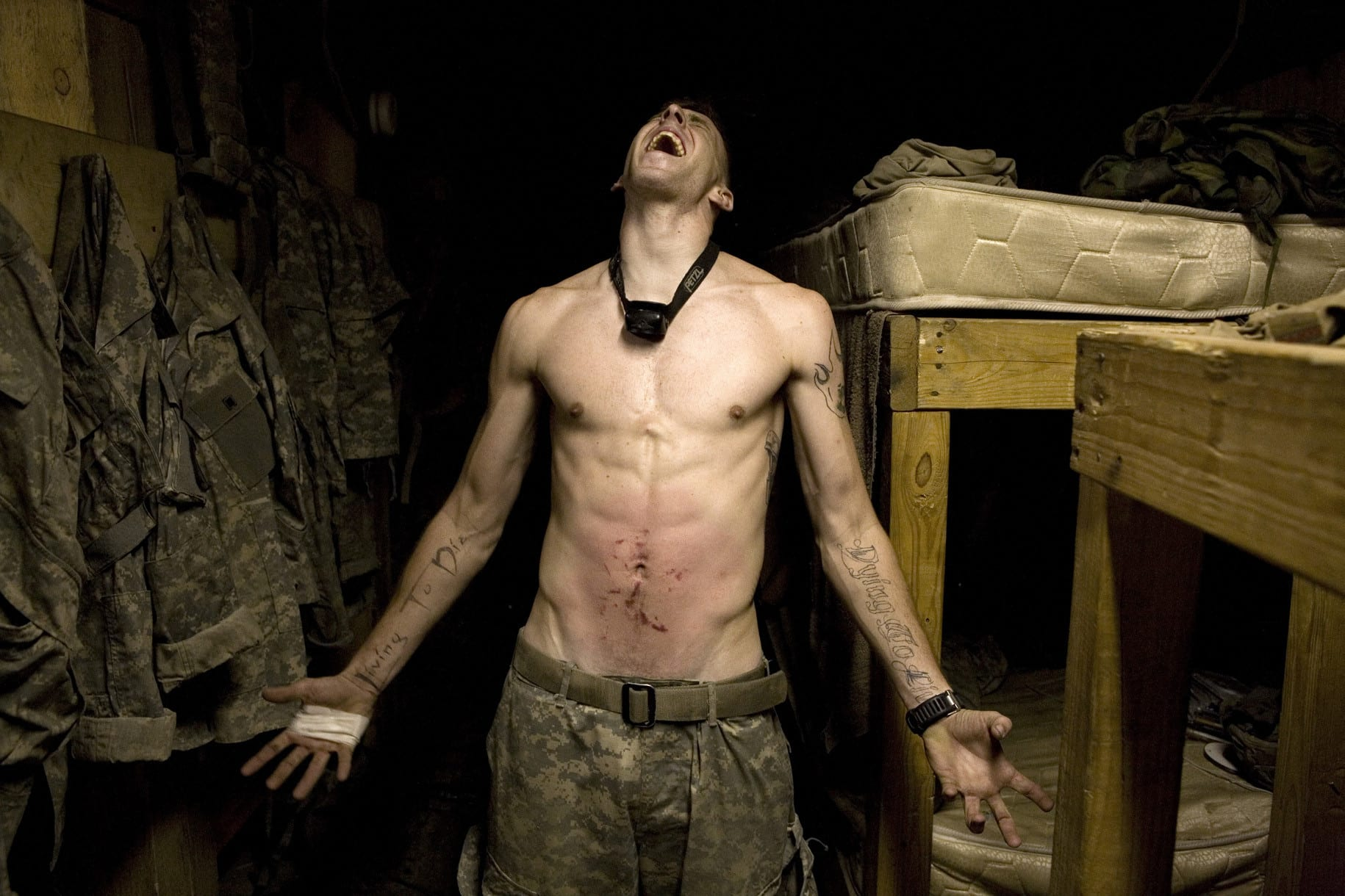 Specialist Tad Donoho screams with pain following being administered a 'pink belly' for his birthday. Each member of the platoon strikes his stomach until blood can be seen to rise, hence the name 'pink belly'. Korengal Valley, Kunar Province, Afghanistan. July 2008.