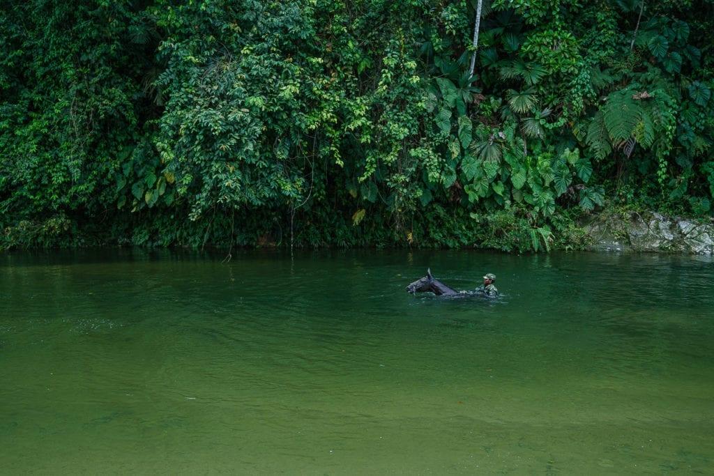 A FARC rebel rides a horse through a river and towards a clandestine route hidden in the mountains. 2 May 2016. Photo © Federico Rios