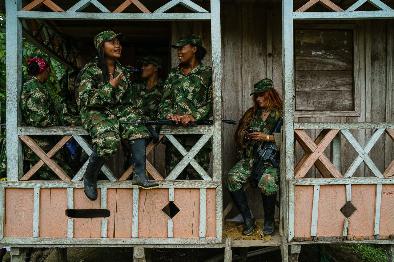 Female FARC rebels sit and watch while the men play a football match against civilians. 3 May 2016. Photo © Federico Rios