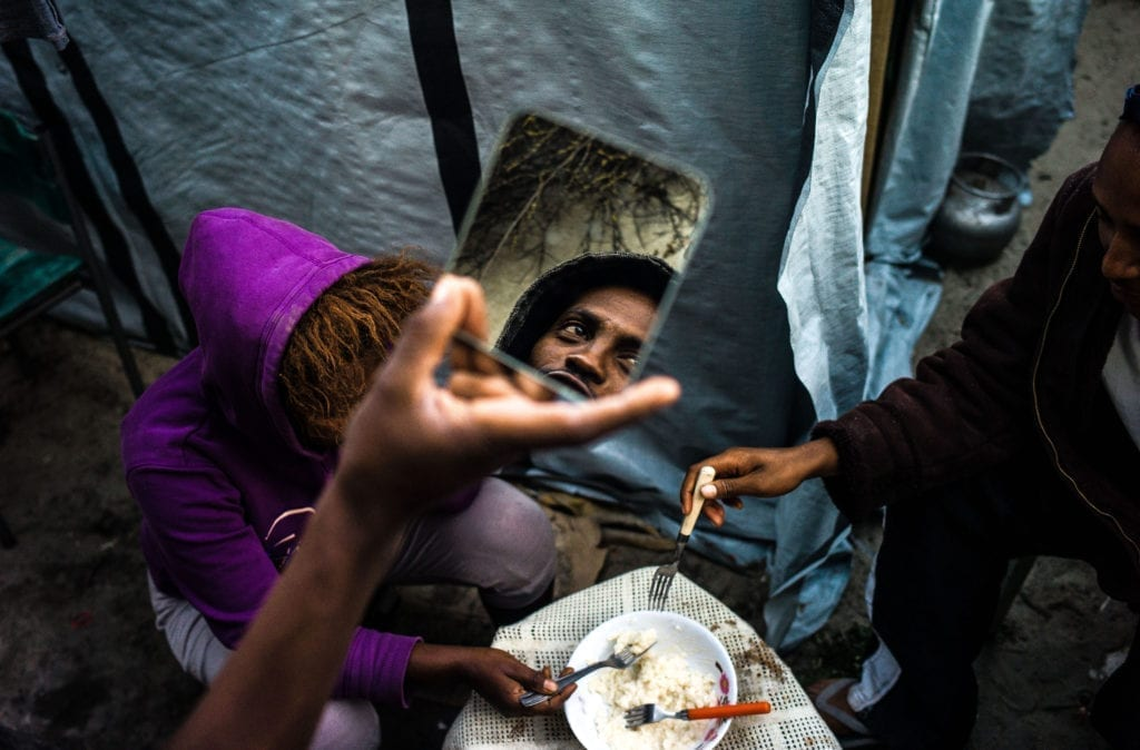 Programme Name: Exodus: Our Journey to Europe - TX: n/a - Episode: n/a (No. 3) - Picture Shows: refugees sharing a meal in the Calais Jungle. - (C) Gus Palmer / KEO Films - Photographer: Gus Palmer