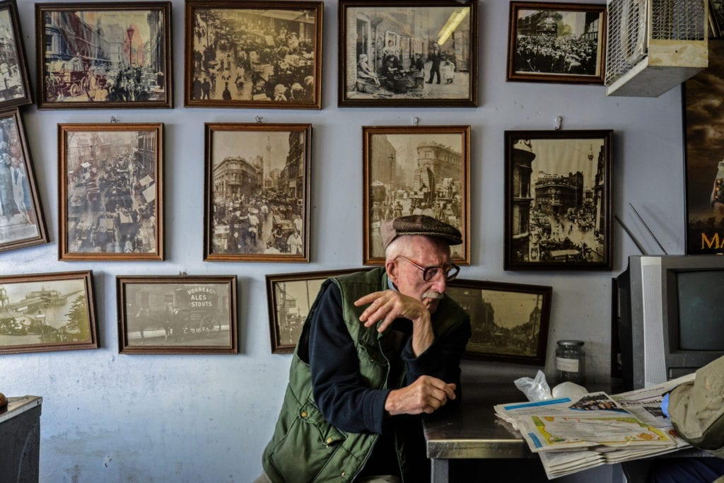 Disappearing Home-London East End's English community. 15. Mr Broomfield, fishmonger and former photographer, surrounded by his photographs of the London old Billingsgate Fish Market at the George's Plaice, Roman Road, Bow on the 11th March 2015, London.