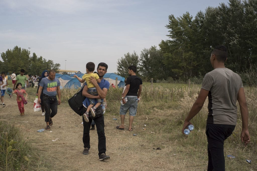 SERBIA, Horgos. September 16, 2015. Mohammed carries Brahim from the closed Serbian-Hungarian border after a rapid dash through Macedonia and Serbia. The border has closed at midnight the previous day, but Mohammed and the group hoped that it would be opened again. It quickly became clear that it wouldn't reopen and the next morning they left for Croatia.