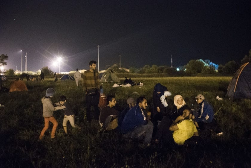 SERBIA. Horgos. 2015. Mohammed stands while Ali and Sidra play at a campground near the closed Serbian-Hungarian border after they made a rapid dash through Macedonia and Serbia.  The border has closed at midnight that day, but Mohammed and the group hoped that it would be opened.  It quickly became clear that it wouldn't reopen and the next morning they left for Croatia.