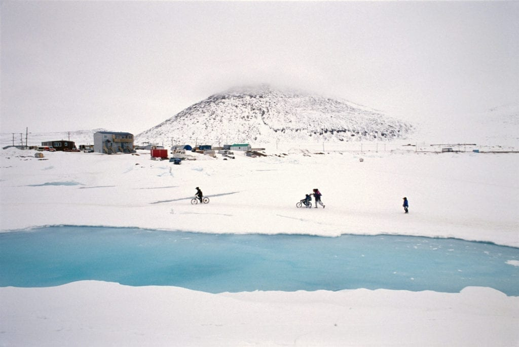 CANADA. Nunavut. Qikiqtarjuaq. 2004. A family walking with their baby stroller on the ice of the Qikiqtarjuaq bay. Qikiqtarjuaq, like many Inuit villages, was a result of forced settlement of nomadic communities. Many of their problems are born from the very difficult transition from nomadism to a permanent, as found 'in the south'.