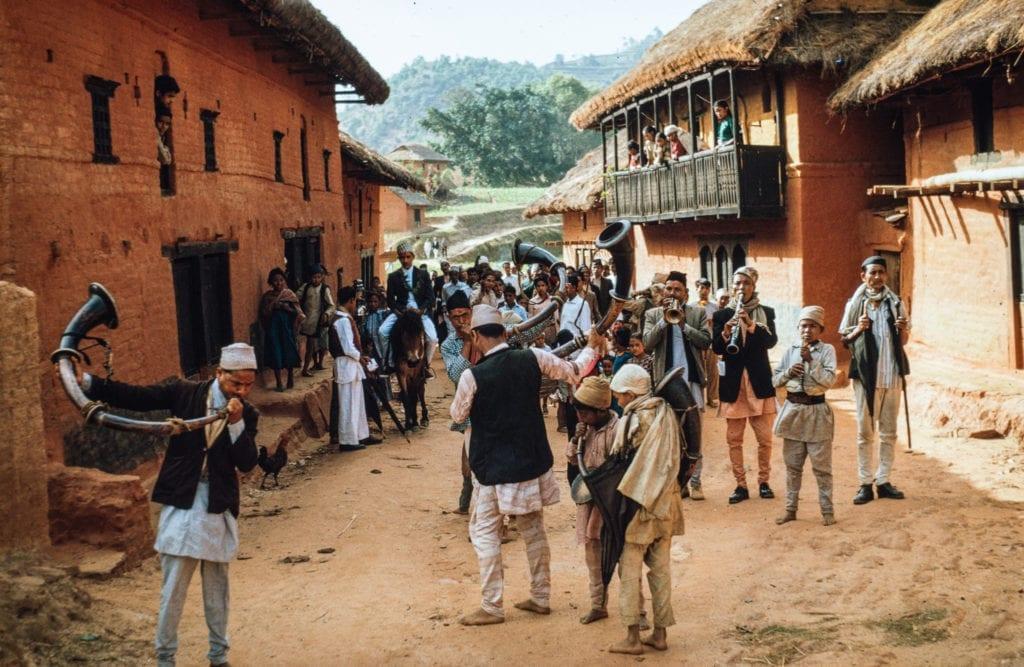 Date: 1964 Location: Bhojpur Description: A Damai ensemble leads a festival procession through a small village bazaar in Bhojpur district.